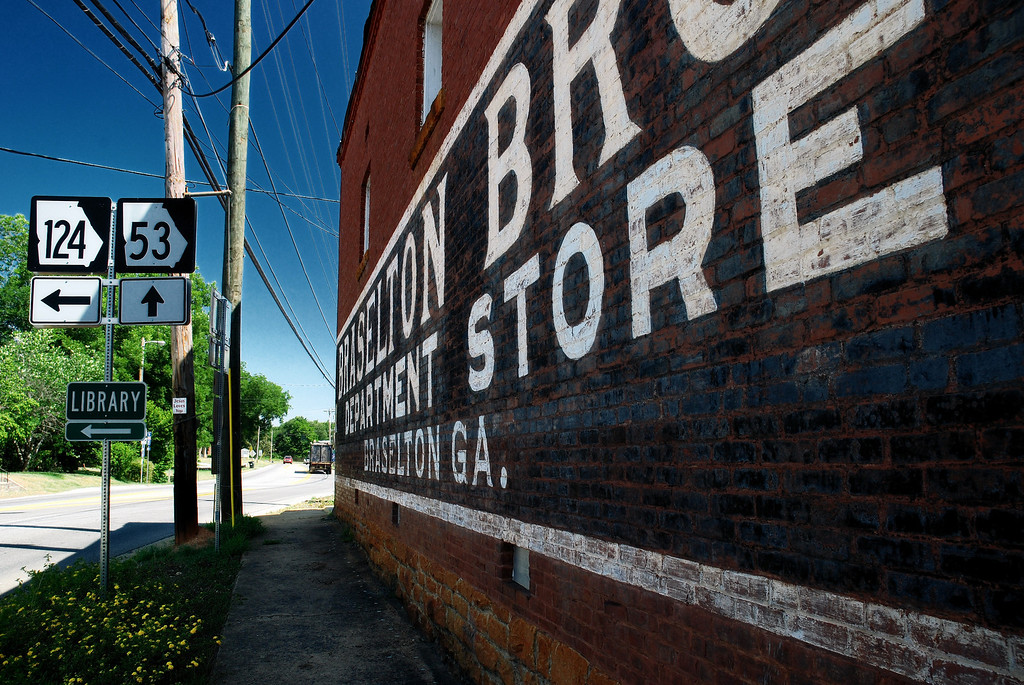 Braselton, GA (Jackson County) June 2008<br /> <br /> In 1887, eight-year-old John Oliver started selling things to his father's field hands. His first inventory included a few cans of food, snuff, and rock candy, with a total value of $ 3.50. Eventually, his brothers Green and Henry joined him;  being very business savvy and treating everyone with the same kindness and respect, the three brothers' reputation and business grew rapidly and in 1904 they moved into a new brick building,  built in five months by S.B. Baker and equipped with modern fixtures and amenities. <br /> <br /> The store had three departments:  dry goods and shoes; clothing and millinery; and groceries. The brothers would periodically travel to New York and other regions to purchase goods, always paying cash. <br /> <br /> Conveniently located at a crossroads and not far from the railroad line in Hoschton, the store prospered and was later passed on to the brothers' sons, however, it fell victim to the modern malls and closed its doors after 103 years of business. Today, it is occupied by an antique shop and the Ceramic Tile Outlet.