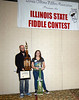 Fiddle Teacher Shawn Drake (L) holds Georgia Rae's Trarveling Trophy and Illinois Grand Champion certificate. Georgia Rae (R) stands behind her first place trophy