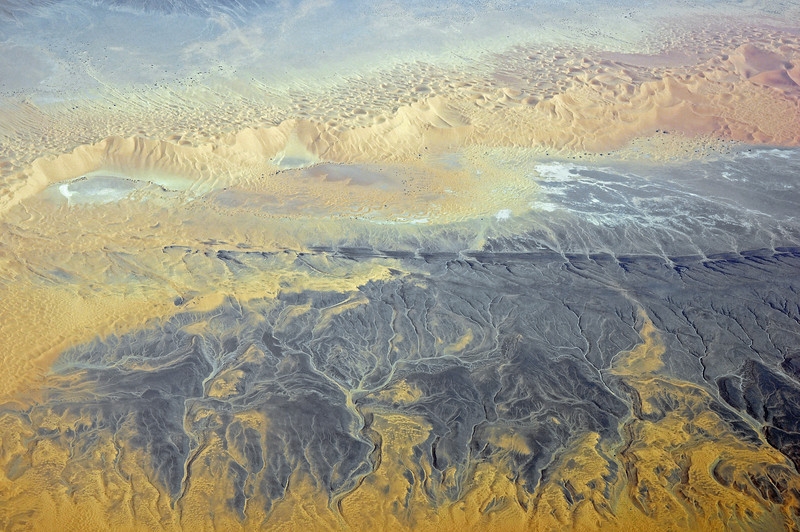 Sand dunes onlapping low mountain ridge in the Sahara, southern Algeria