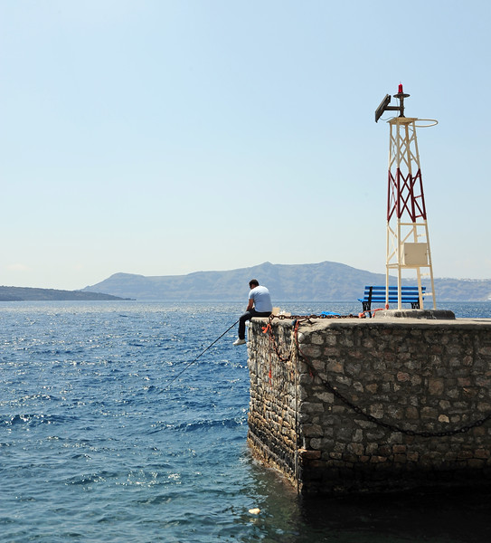 Fishing in the volcanic crater of Santorini from the breakwater at Fira's old port, Greece