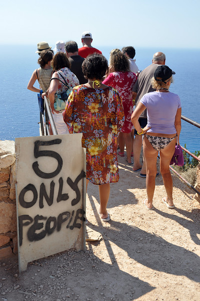 Risky behaviour at high cliff-edge viewpoint over Navagio Bay in west Zakynthos, Greece
