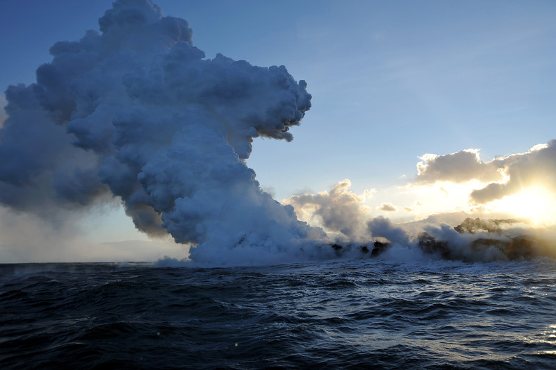 Steam explosions and large plume cloud ('laze') formed by red-hot lava, derived from fissures associated with the Kilauea volcano, flowing into the Pacific Ocean along the southern shore of Big Island, Hawaii