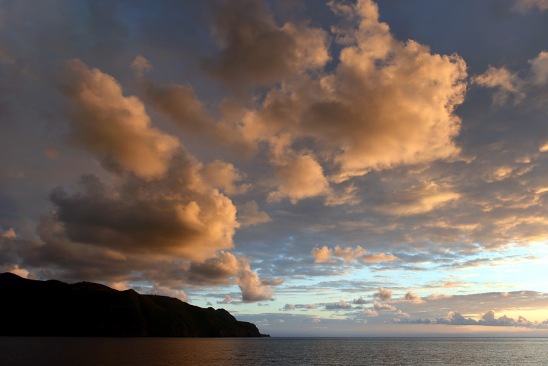 Sunset rays illuminating cloud formations above the island of Lipari, Italy
