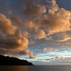 Horizontal sun rays illuminating clouds above the island of Lipari, Italy