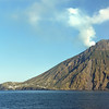 The village of Ginostra below the smoking summit (918 m) of the volcano of Stromboli, Italy