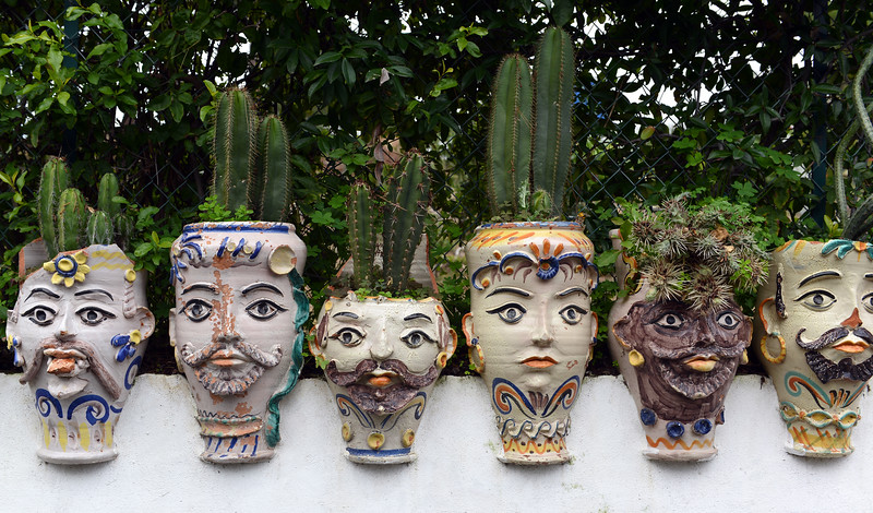 Artful clay pots along garden wall on the island of Vulcano, Italy
