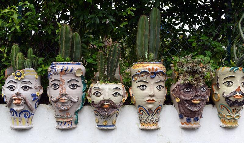 Artful clay pots along garden wall on the island of Vulcano, Italy