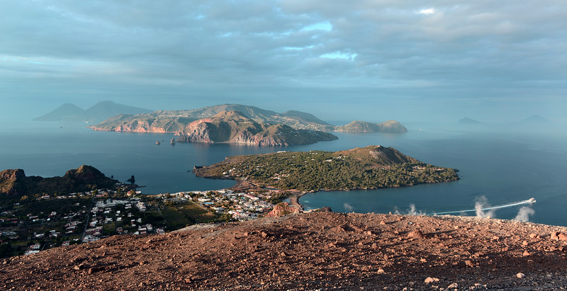 View from steaming crater edge over village of Vulcano Porto, with Lipari and other Eolian islands in the background