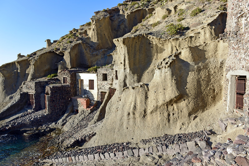 Boat houses in steep volcanic cliffs at Punta Perciato on Salina island, Italy