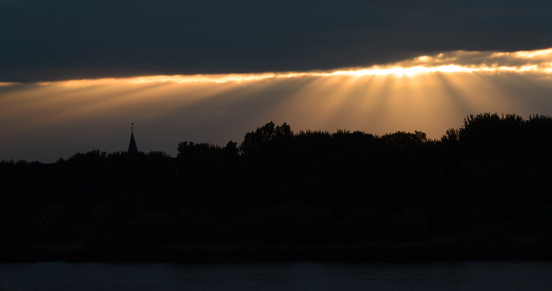 Sunrays breaking through cloud cover over the village of Warmond, The Netherlands