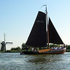 Traditional Dutch 'botter' wooden sailing barge passing windmill 'De Kok' at the Kagerplas, The Netherlands