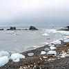 Ice blocks stranded on pebbly beach along the outer Hornsund, Svalbard