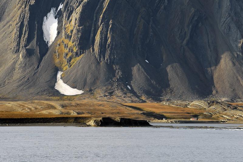 Historical wooden cabins at Ahlstrandhalvøya, below vertical rock layers of the Aldegondaberget (596 m) in the southern Van Keulenfjorden, Svalbard