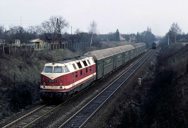 Deutsche Reichsbahn 118 029, east Berlin ring line, Fri 11 February 1977.  The B-B diesel-hydraulic heads a train of double-deck coaches out of east Berlin.  Photo by Les Tindall.