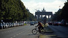 Morning bike commuter crosses Street of 17 June behind Brandenburg Gate