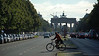 Morning bike commuter crosses Street of 17 June behind Brandenburg Gate