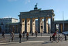 Tourist watches bike commuters come through Brandenburg gate