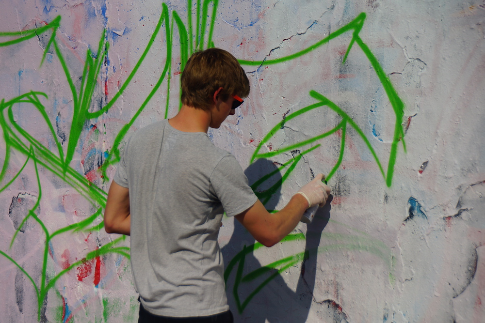 An urban street artist designing art on the wall of Mauerpark.