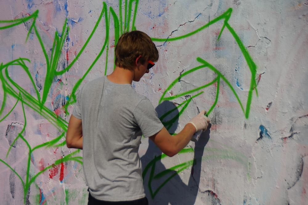 An urban street artist designing art on the wall of Mauerpark.