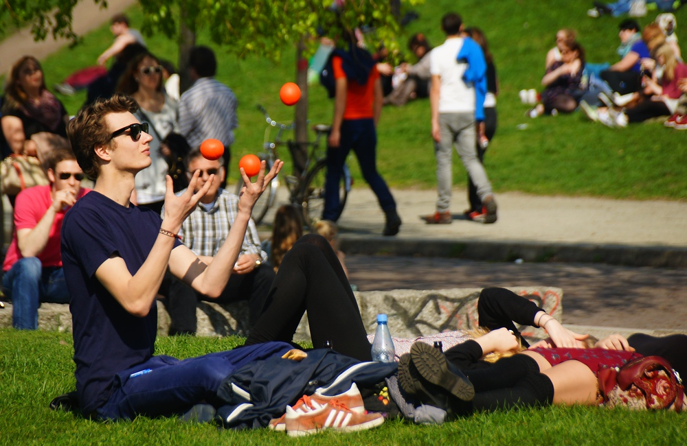 This young man was showing off his impressive juggling skills while sitting down on the grassy field of Mauerpark.