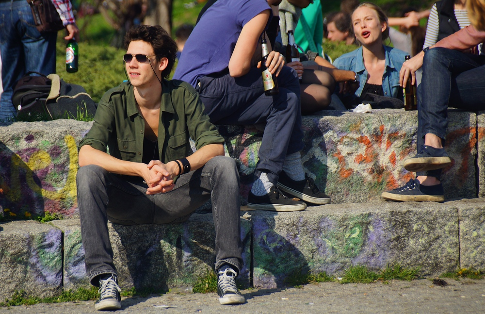 A young guy just chilling out while a group behind him share beers.