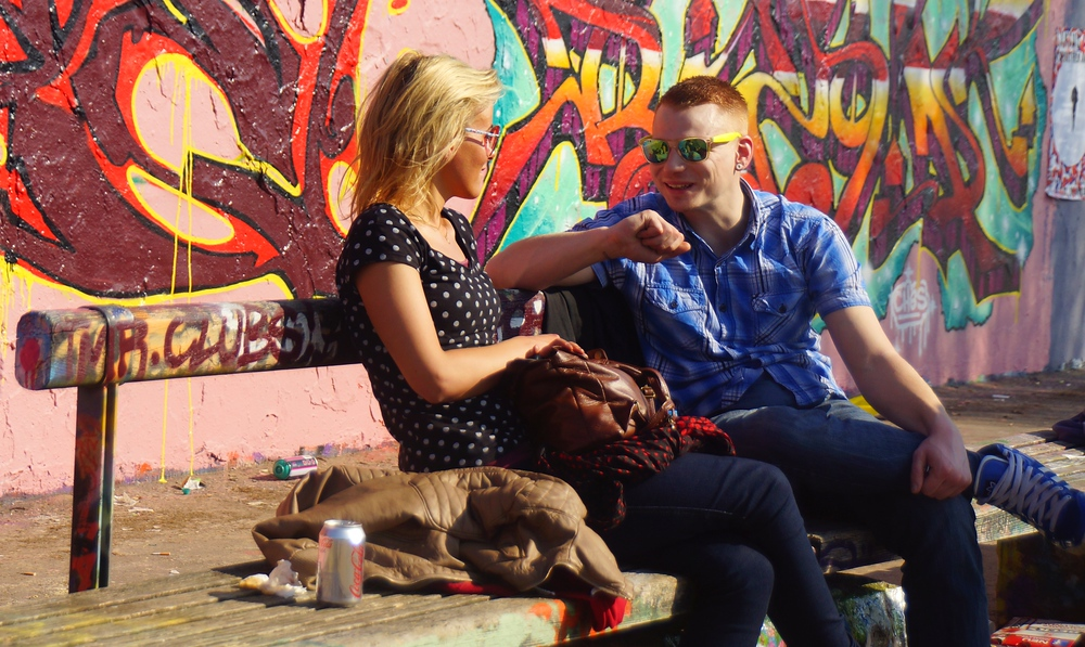 A snapshot of a young lady and man sharing a conversation alongside the wall of Mauerpark.