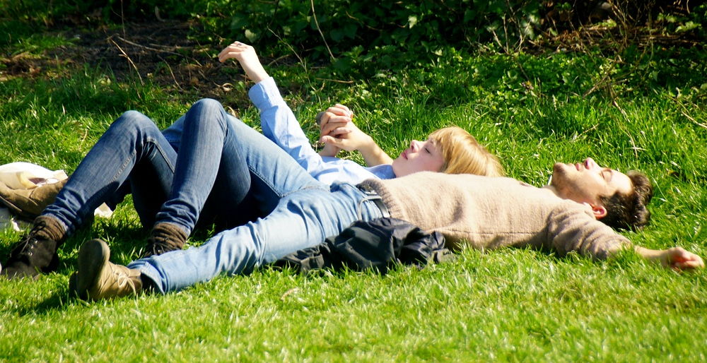 A young couple lying down on the grass soaking up the sun and atmosphere from the live musical performances.