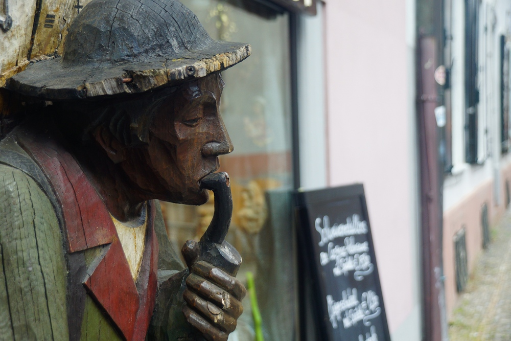 A wooden sculpture of a man smoking a pipe just outside of a restaurant / bar in Freiburg, Germany.