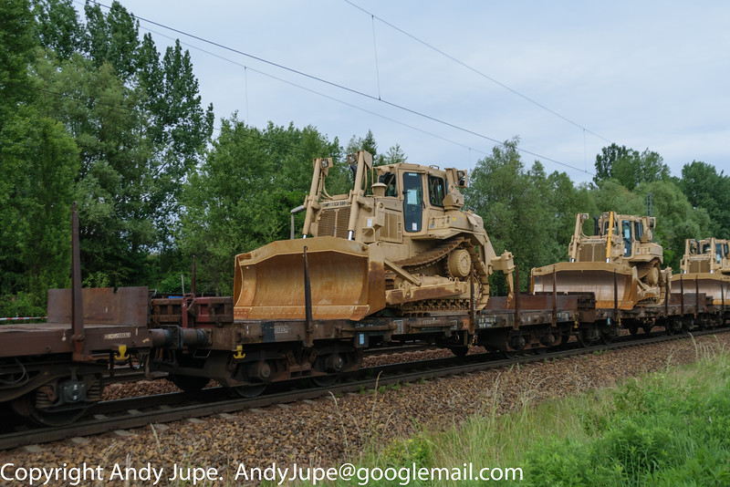 An earth mover allocated to the US Army (15th Engineer Battalion) / 18th Military Police Brigade) heads East through Leipzig Thekla station on board wagon Rmms 31 80 3962 442-0 on Tuesday the 9th of June 2015