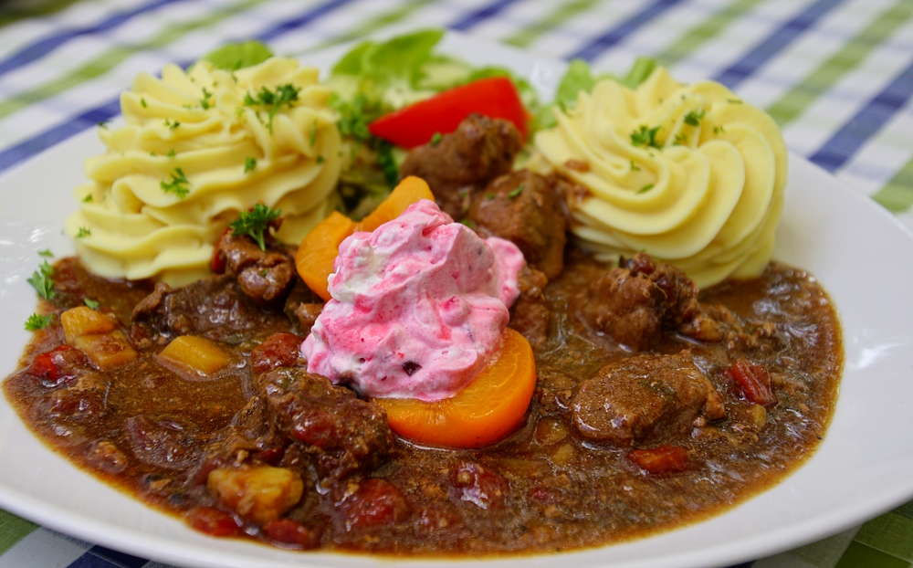 A delicious plate of wild game goulash, cranberries, whipped cream and mashed potatoes in Spreewald, Germany