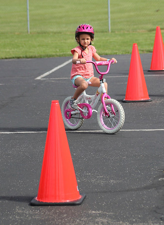 Roger Schneider | The Goshen News<br /> Avery Wills, 3, Goshen, rides her bicycle through an obstacle course set up at Shanklin Park as part of the GetUP and GOshen wellness event Saturday.