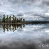 """The point, with a thin line of trees, extends into the middle of the Ottawa River. Glasslike reflections on a windless morning. Pinhey's Point Heritage Property and Park. <a href=""""http://www.gettyimages.ca/detail/photo/pinheys-point-heritage-property-and-park-royalty-free-image/166549519"""" target=""""_blank"""">License this photo on Getty Images</a> © Rob Huntley 2012"""