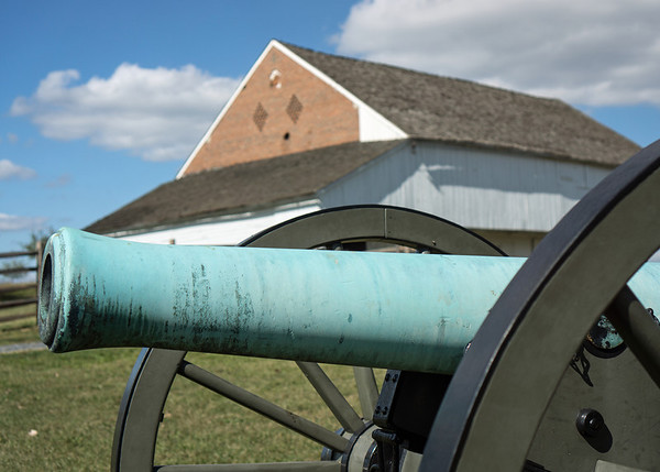 Napoleon On Guard: a bronze Union cannon at Trostle Farm south of Gettysburg.  Confederate troops overran the Federal artillery position here on day two of the battle.  The black spot you see on the end of the barn is the hole of a cannon shot.