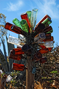"Ghost town Bottle tree Randsburg CA. From www.felderrrushing.net Although glass was made deliberately as early as 3500 B.C. in northern Africa, hollow glass bottles began appearing around 1600 B.C. in Egypt and Mesopotamia. Clear glass was invented in Alexandria around 100 A.D. Soon around then, tales began to circulate that spirits could live in bottles - probably from when people heard sounds caused by wind blowing over bottle openings. This led to the belief in ""bottle imps"" and genies (from the Arabic word djinn) that could be captured in bottles (remember Aladdin and his magic lamp? This story originated as an Arabian folk tale dating back thousands of years, even before clear glass was invented). Somewhere in there, people started using glass to capture or repel bad spirits. The idea was, roaming night spirits would be lured into and trapped in bottles placed around entryways, and morning light would destroy them."