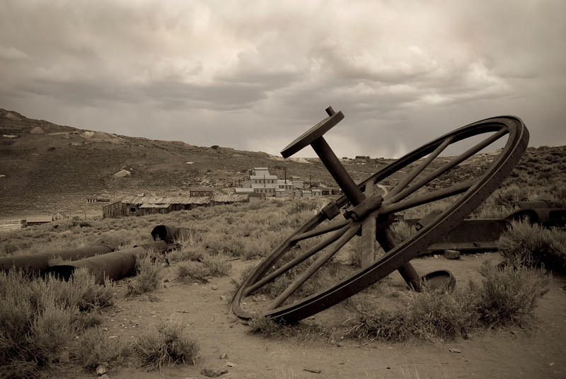 """""""Bodoe Big Wheel"""" a abondoned mill wheel with the town in the background under cloudy skies."""