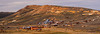 """Vew of Bodie townsite from hill to the southwest, near cemetery. Bodie is named after Waterman S. Body, who discovered gold here in 1859. He and his partners built a small cabin in the area. The winter of 1859 was severe, and Body died in a snowstorm while trying to get supplies. His body was recovered in 1860 when the snow melted. The spelling of the town's name was changed to insure proper pronounciation. By 1879 the town had a population of over 10,000. Killings were daily events, and bodie had the reputation as the roughest town in California. A famous story of Bodie is of a little girl who, upon learning he parents were taking her to Bodie, wrote in her diary, """"Good-bye God, I'm going to Bodie."""" When the story spread and a Bodie newspaper writer learned of it, he put a spin on the story that the girl had actually written, """"Good! By God, I'm going to Bodie!"""" At and elevation of 8,375 feet, Bodie was said to have """"the worst climate out-of-doors."""""""