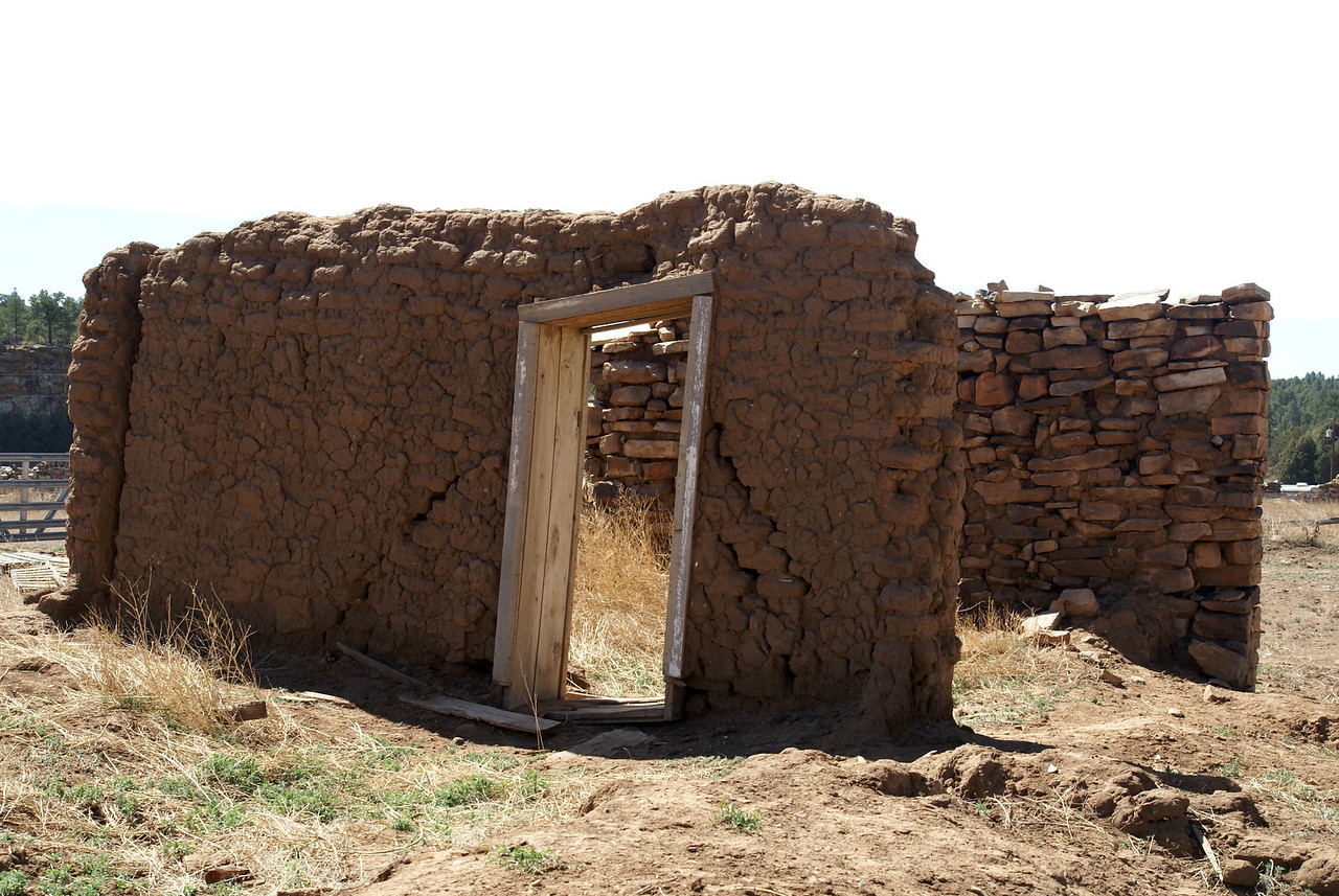 Stone building covered with adobe walls.