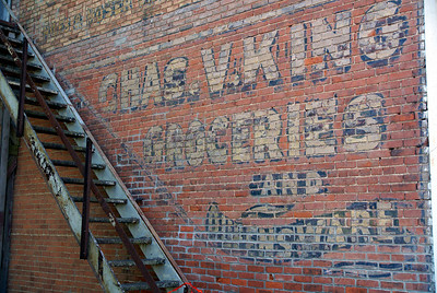 This is only a partial view of the ghostsigns on this wall.  I was looking into the sun and could not get a very good photo of the upper ghostsign so the bottom one will have to do for now. Burlingame, KS,