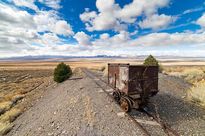 Old mining ore cart on tracks underneath a beautiful blue sky with clouds in the Nevada desert at the Berlin Ghost Town.