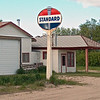 This was my Grandfathers Standard Oil station. The large garage edition on the left was not there till many years later. I will be uploading pictures of my Dad as a Teen with his friends watching over the station and goofing off!  My grandfather also had the Oil Delivery and Sold Fords from this Building. He would take orders and go get the cars from Grand Forks and sometime right from the Factory in Fargo!  He build a big new station directly across the street which then burned to the ground. To the right was a Lumber Yard and the Jail sat just on the otehr side of the Bushes, and then a nice city park.  We used to have fun playing around that old jail.
