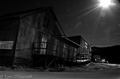 The moon and the stars light an old car and building