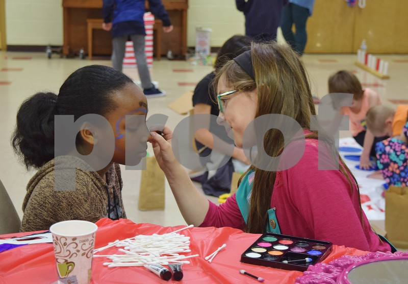 Eleven-year-old Alora Ager, a Girl Scout Junior with Troop 1058 (right), paints the face of 9-year-old Kimani Smith during Saturday's free children's carnival the scouts hosted at First Lutheran Church in DeKalb. In lieu of an entrance fee, the troop collected fleece clothing items, fleece blankets, rain coats, rain boots and Croc-style shoes to help rural villagers in Madagascar.
