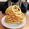 """4/14/2009 <br /> <br /> """"Everything is bigger in Texas"""" and these onions rings are as Texas as cowboy boots and barbecued brisket! (best friend at table)<br /> <br /> Cheddars Casual Cafe' <br /> Dallas, TX"""