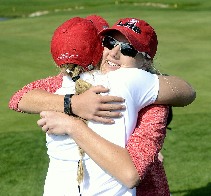 Loveland's Lauren Lehigh hugs teammate Aili Bundy after paring the final hole of the 4A State Girls Golf Tournament at Colorado National Golf Club in Erie. Lehigh won the individual title by one stroke over Bundy and Glenwood's Springs Lauren Murphy, with the Indians winning their first team title in the sport.