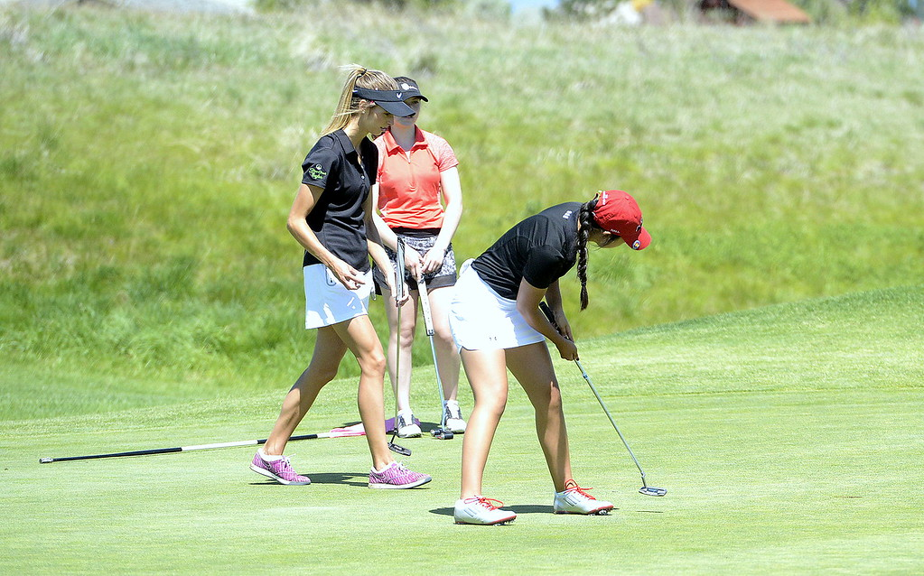 . Loveland\'s Natalee Hall watches her putt drop during Monday\'s first round of the 4A state golf tournament at Colorado National Golf Club in Erie.
