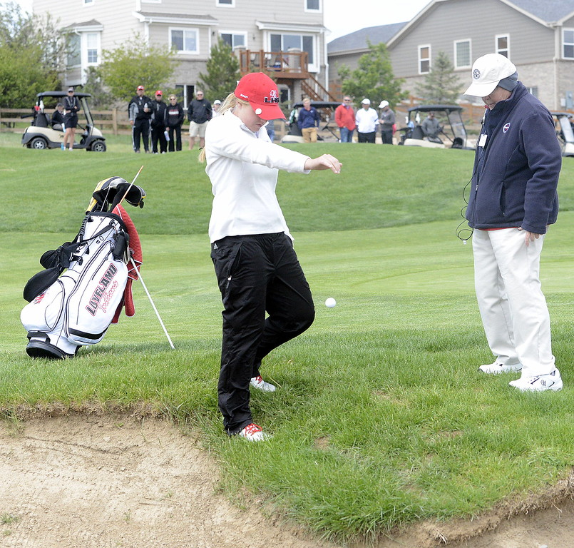 Loveland's Aili Bundy takes a drop as an official looks on after her ball became embeded in a hole near a green-side bunker during the second round of the 4A State Girls Golf Tournament on Tuesday at Colorado National Golf Club in Erie.
