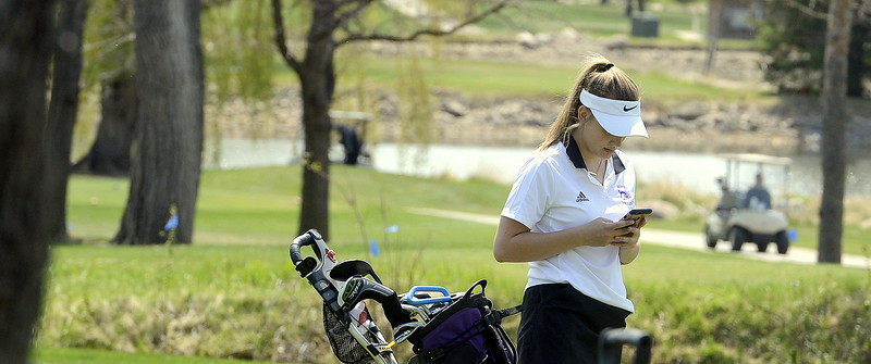 Mountain View's Ally Buckner checks her phone  during Monday's Northern Conference league meet at the Olde Course in Loveland. (Mike Brohard/Loveland Reporter-Herald)