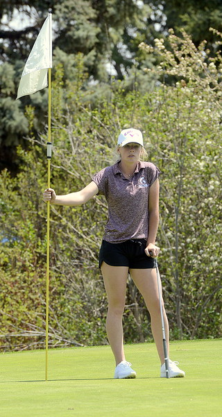 Stephanie Haberkon of Berthoud tends the flag as one her playing partners putts  during Monday's Northern Conference league meet at the Olde Course in Loveland. (Mike Brohard/Loveland Reporter-Herald)