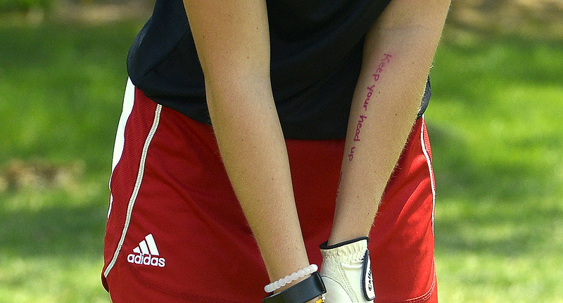 """Lauren Lehigh of Loveland wrote a couple of reminders for herself on the inside of her left arm during Monday's Northern Conference league meet at the Olde Course in Loveland. In addition to keeping her head down, she jotted in pink ink that """"calm is your super power"""" and """"calm + confident."""" (Mike Brohard/Loveland Reporter-Herald)"""