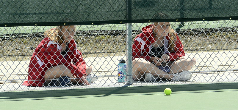 Loveland's No. 3 doubles team Rebecca Emme (left) and Allison Westbrook peek through the fence to watch teammate Ava McQuade play for the 4A Region 4 title at No. 3 singles Friday at North Lake Park. (Mike Brohard/Loveland Reporter-Herald)